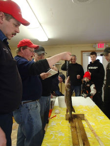 people measuring fish
