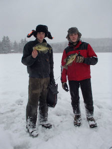 two boys holding fish in the snow